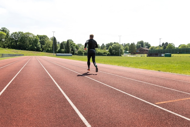Full shot man with prosthesisrunning outdoors