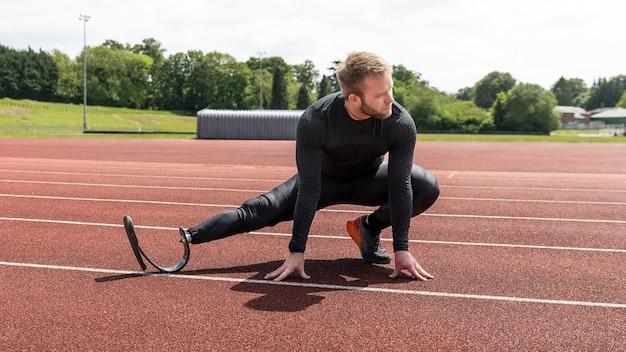 Full shot man with prosthetic leg stretching on running track