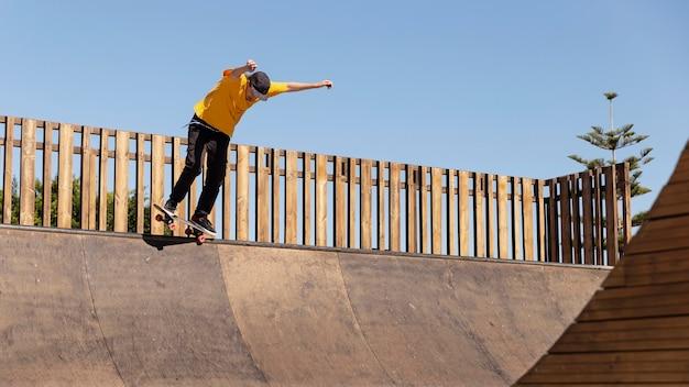 Полный выстрел человек со скейтбордом, весело