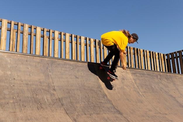 Полный выстрел человек с прыжками на скейтборде