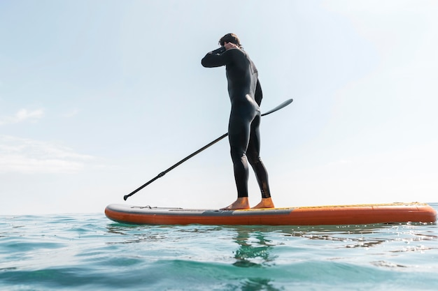 Full shot man with suit on surfboard