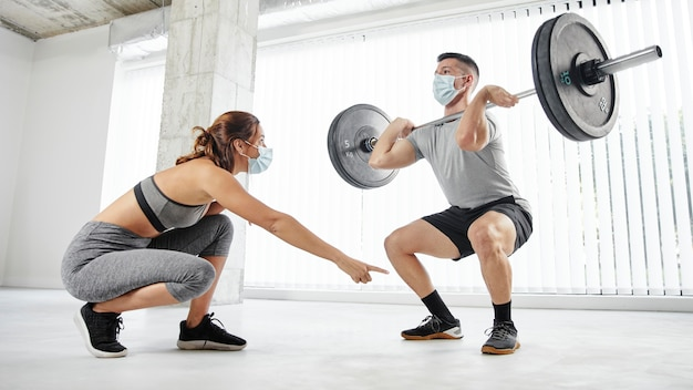 Full shot man and woman training with masks