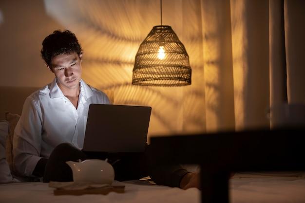 夜自宅で働くフルショット男