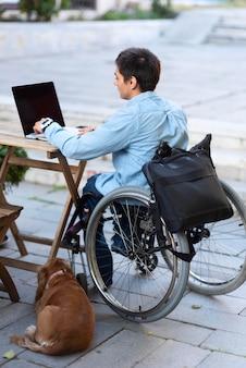Uomo pieno del colpo che lavora al computer portatile
