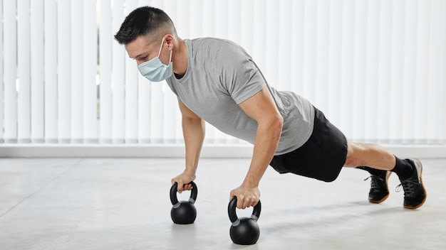 Full shot man working out with mask