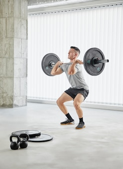 Full shot man working out with weights