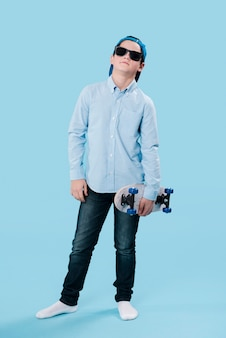 Full shot of modern boy with skateboard