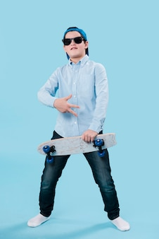 Full shot of modern boy with sunglasses and skateboard