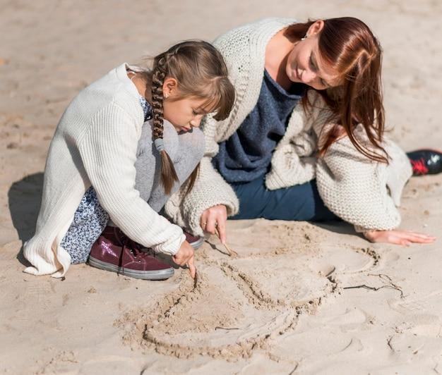 Мать и девочка в полный рост, играя на пляже