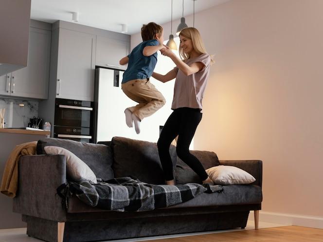 Мать и ребенок в полный рост прыгают на диване