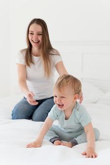 ベッドでフルショットの母親と幼児