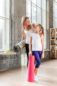 Full shot mother and daughter holding yoga mats looking at each other