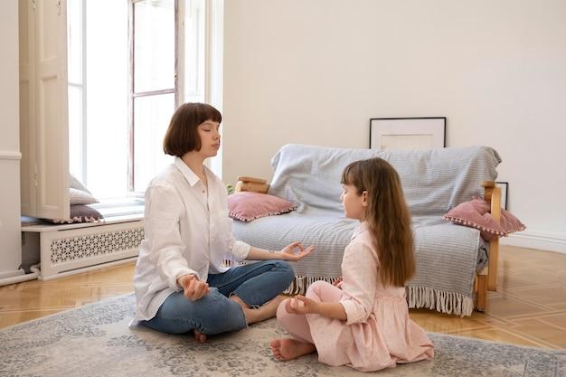 Full shot mother and daughter meditating