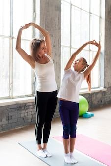 Full shot mother and daughter stretching in gym