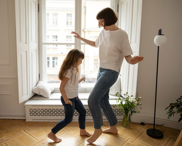 Full shot mother and girl dancing indoors