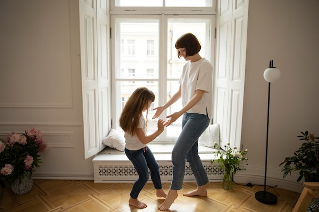 Full shot mother and girl dancing together