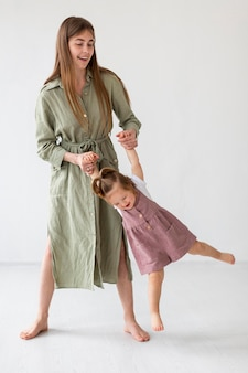 Full shot mother and girl playing