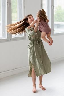 Full shot mother holding up girl
