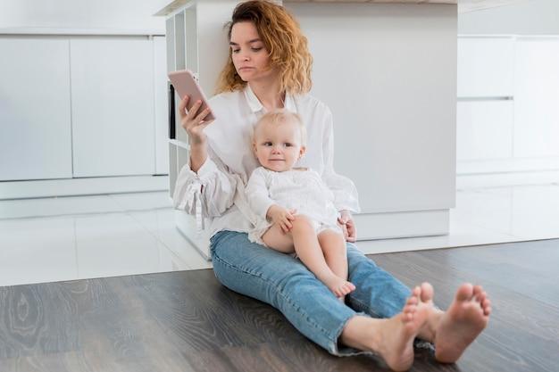 Madre della foto a figura intera che si siede sul pavimento