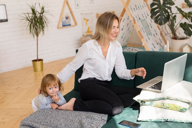 Full shot mother with kid working at home