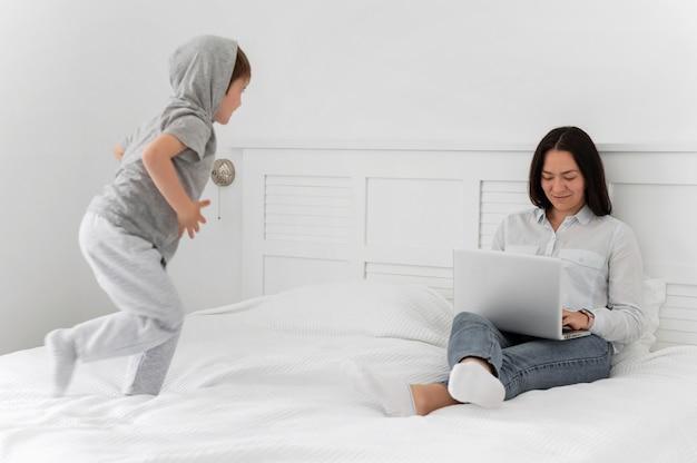 ラップトップとベッドで子供とフルショットの母親