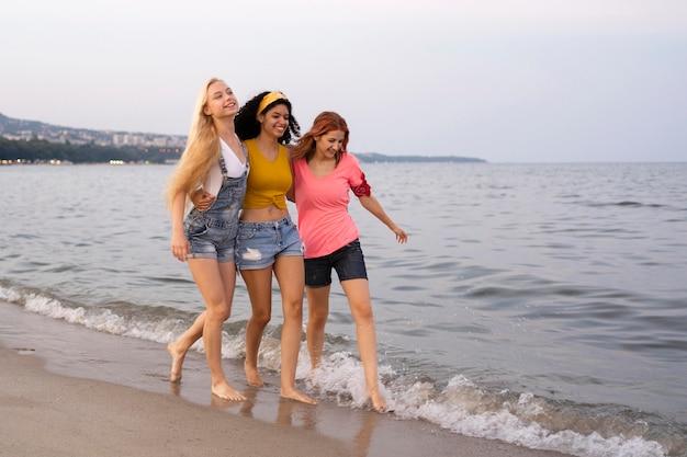 Полный снимок красивых друзей на пляже