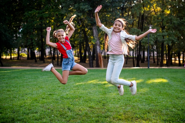 Полный снимок девушек прыгает на открытом воздухе