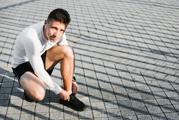 Полный выстрел человека, связывающего его шнурки