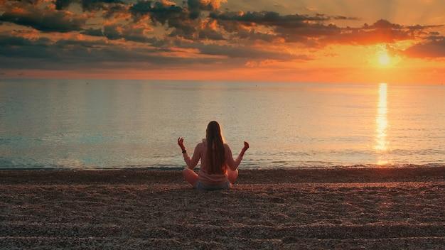 海岸の背面図で瞑想する女性のフルショット