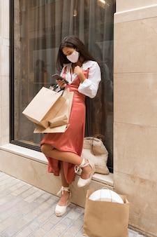 ショッピングバッグとスマートフォンを持つ女性のフルショット