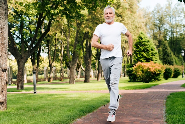 Full shot old man running outdoors