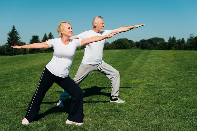 Full shot old people exercising outdoors