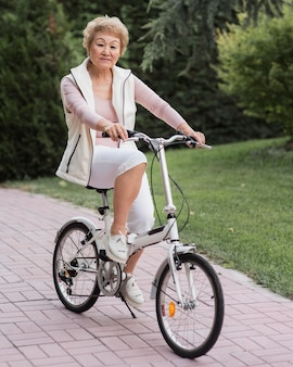 Full shot old woman on bicycle