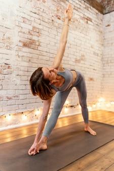 Полный снимок старухи, растягивающейся на коврике для йоги