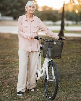 Full shot old woman with bicycle