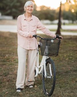 자전거와 함께 전체 샷된 늙은 여자