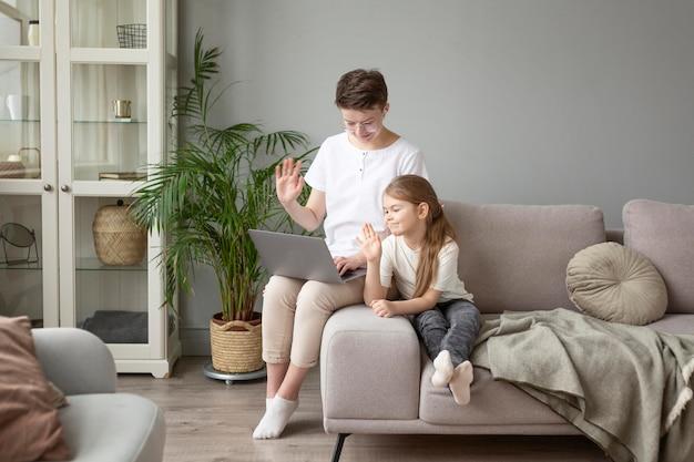 Родитель и ребенок в полный рост машут ноутбуку