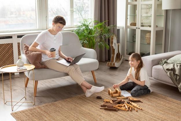 Genitore pieno del colpo con caffè e computer portatile