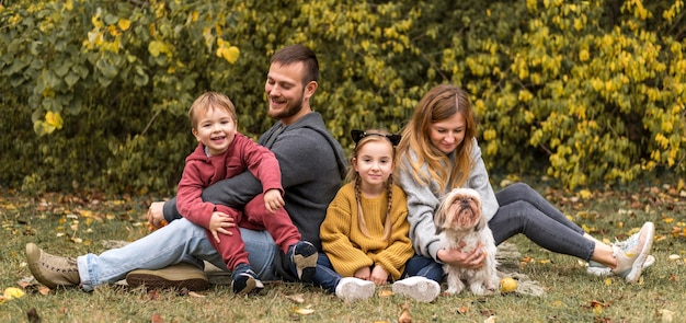 Full shot parents, kids and dog outdoors