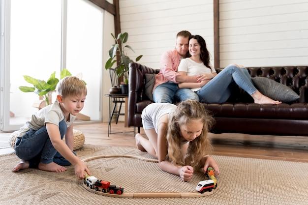 子供が遊ぶのを見るフルショットの両親