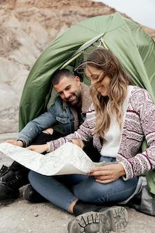 Полный снимок людей, держащих карту на открытом воздухе