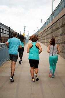 屋外で走っているフルショットの人々