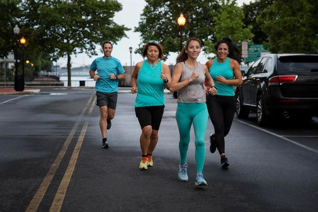 屋外で一緒に走っているフルショットの人々