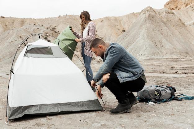 Persone a tutto campo che montano una tenda