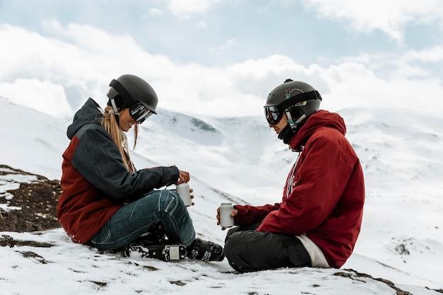 Gente piena del colpo che si siede sulla montagna
