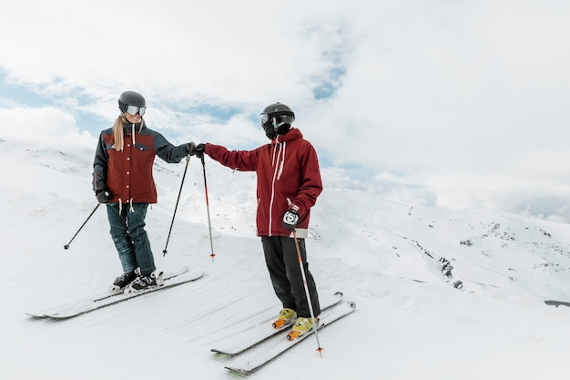 一緒にスキーをするフルショットの人々