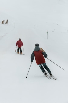フルショットの人々がスキーをする