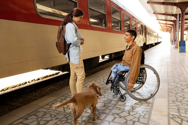 Full shot people at train station with dog