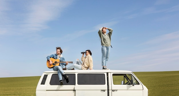 Full shot people on van with guitar