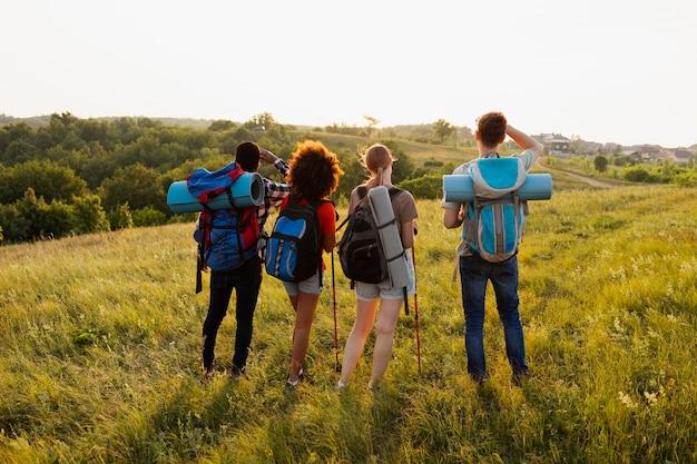 屋外でバックパックを身に着けているフルショットの人々
